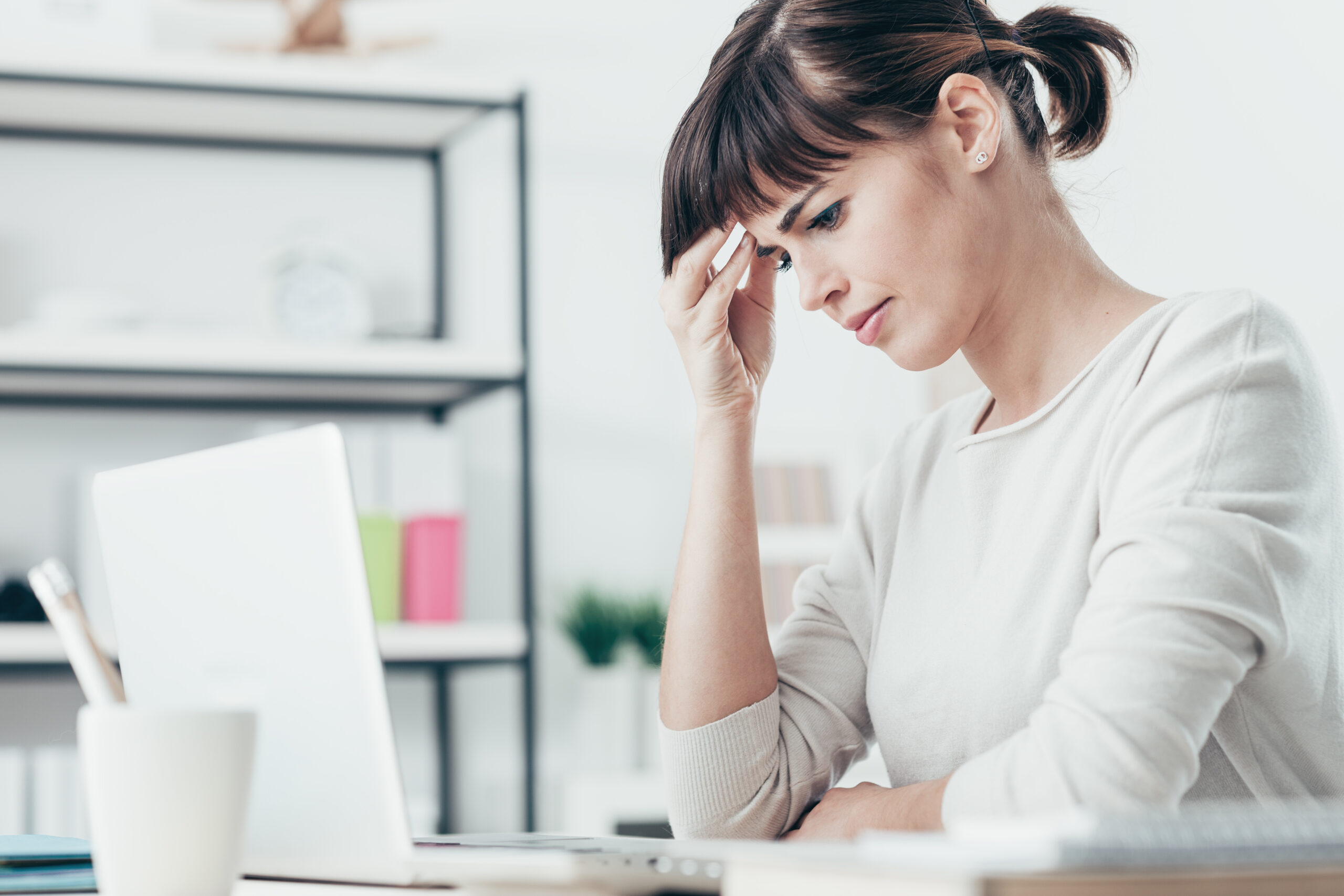 Tired woman having a bad headache, she is sitting at office desk and touching her temple