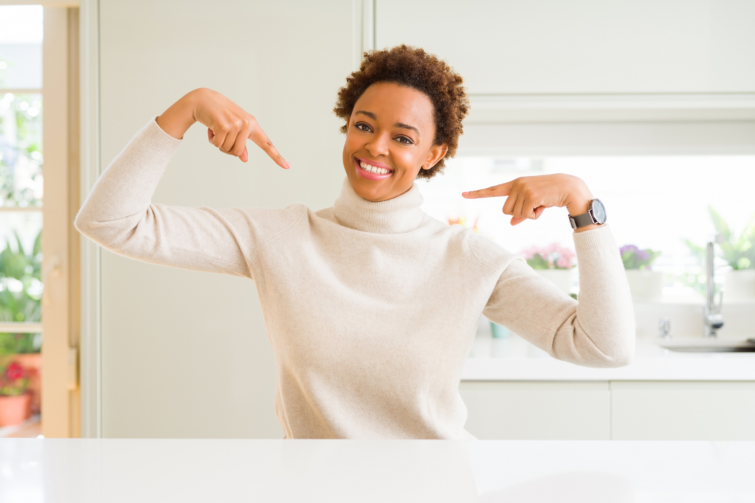 Young beautiful african american woman at home looking confident with smile on face, pointing oneself with fingers proud and happy.